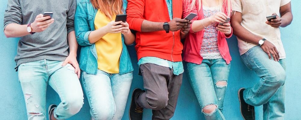 Imagem mostra corpos jovens, todos utilizando smartphones